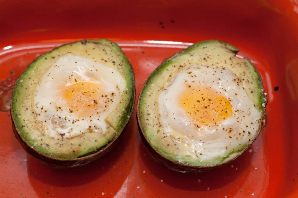 two avocado halves with baked eggs.