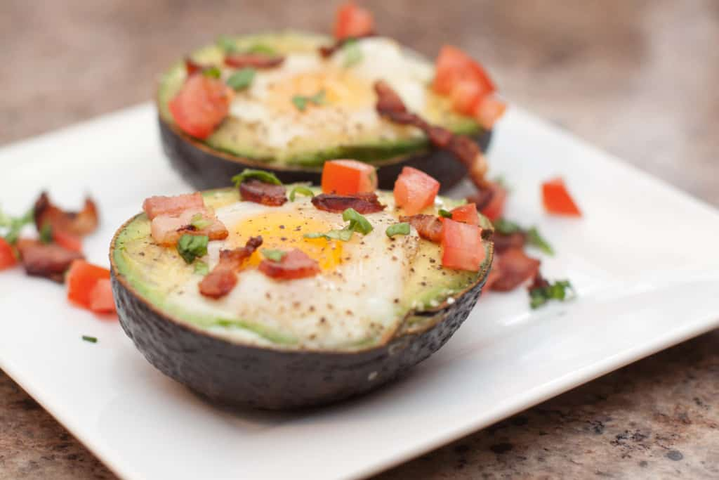 a plate with halved avocado eggs topped with baked eggs and bacon and tomatoes.