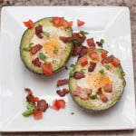 overhead of a halved avocado with eggs and crumbled bacon and tomatoes.