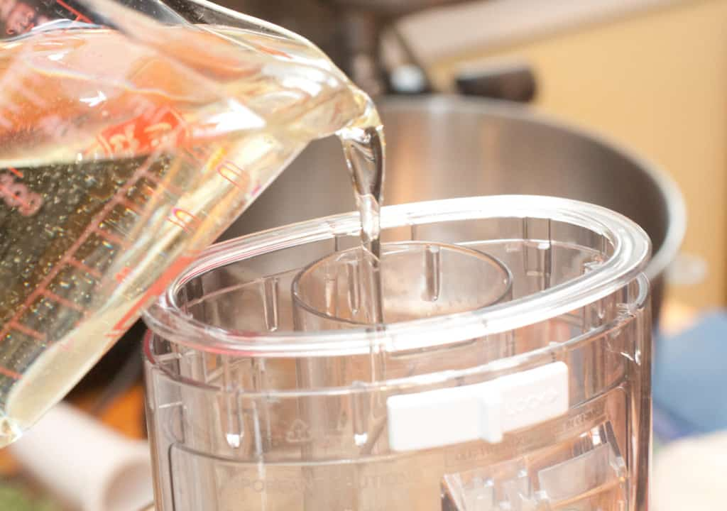 Pouring oil into a food processor.