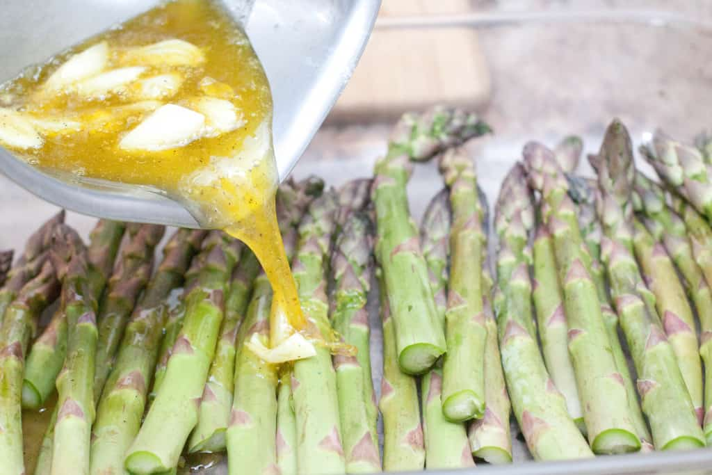 garlic oil being poured on asparagus