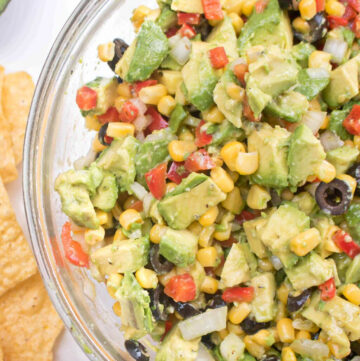 a large bowl of avocado salsa with olive, peppers, and corn.