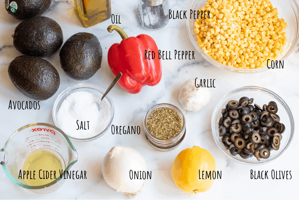 avocados, red pepper, corn, salt, vinegar, onion, lemon, olives, oregano, olive oil, and pepper on a counter.