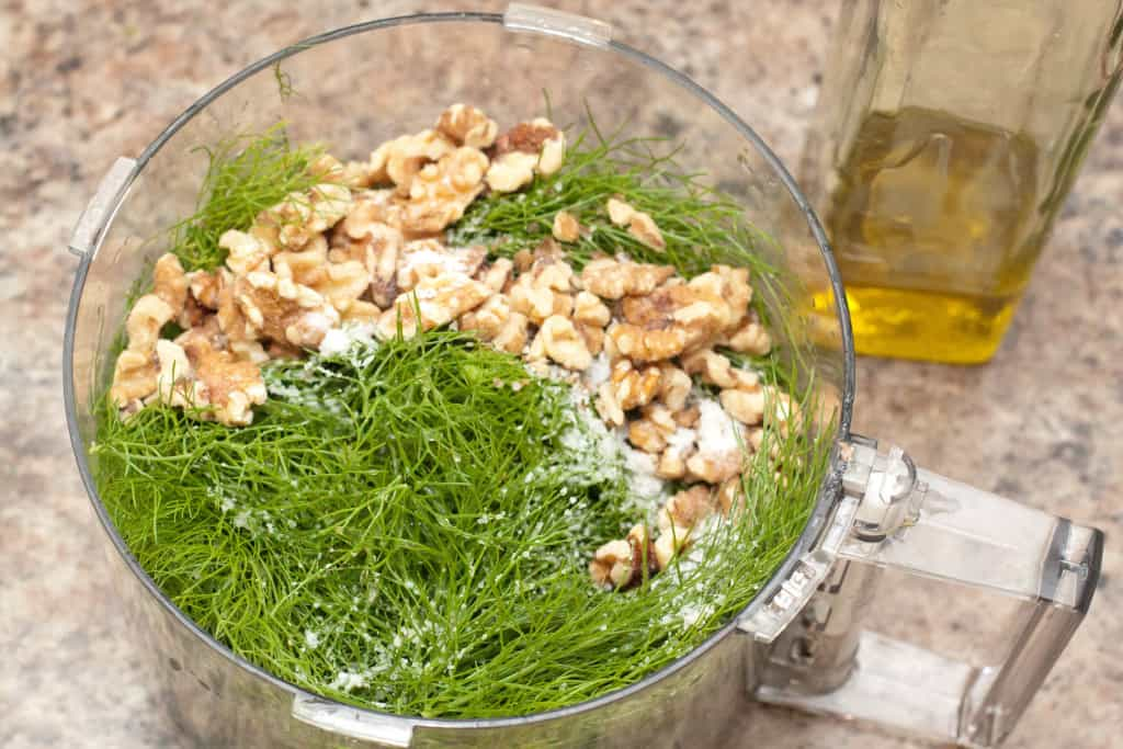 fennel fronds, walnuts, and salt in a food processor.