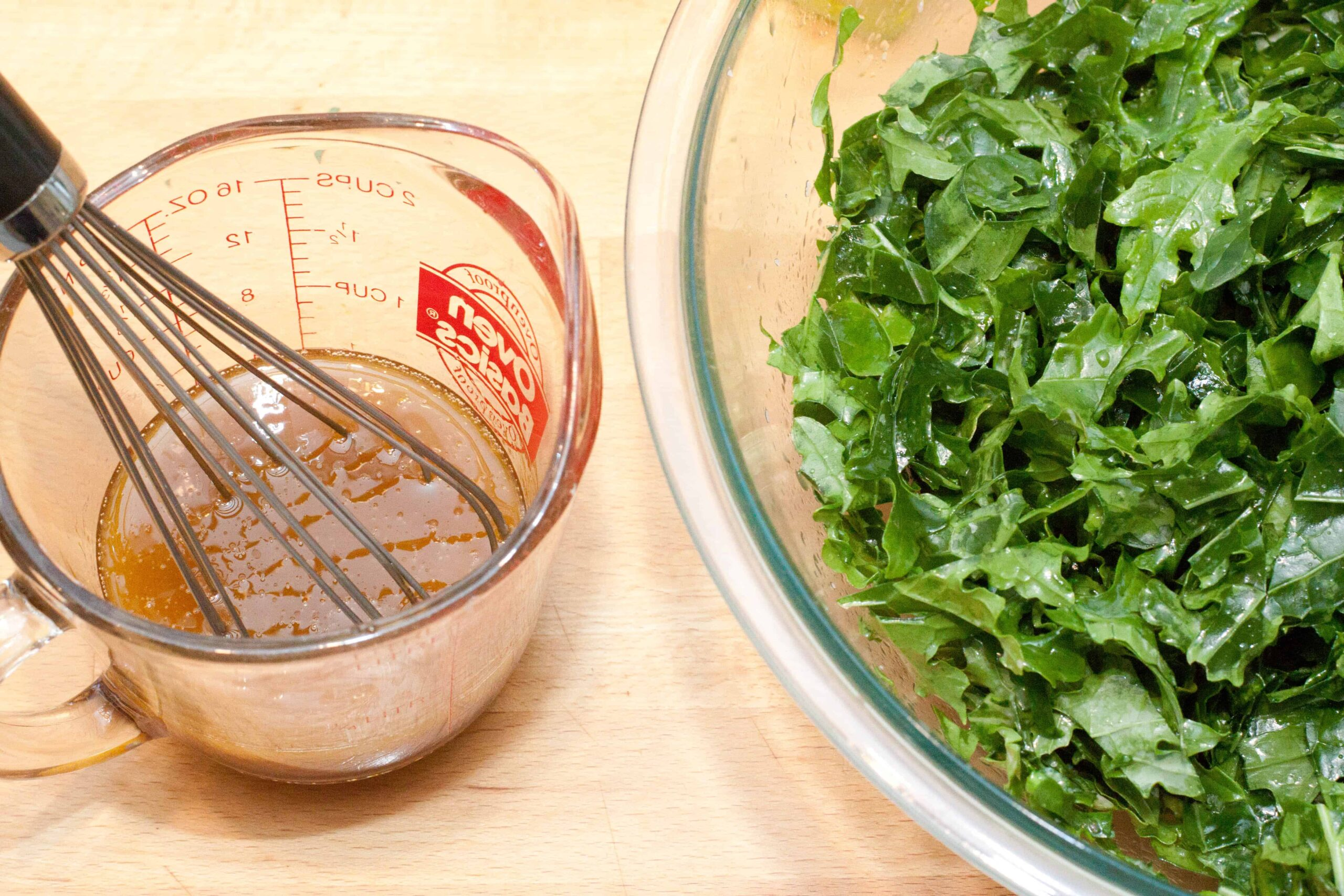 a whisk in a measuring cup with dressing next to a bowl of kale.