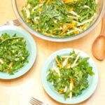 a large bowl of kale salad with two smaller bowls.