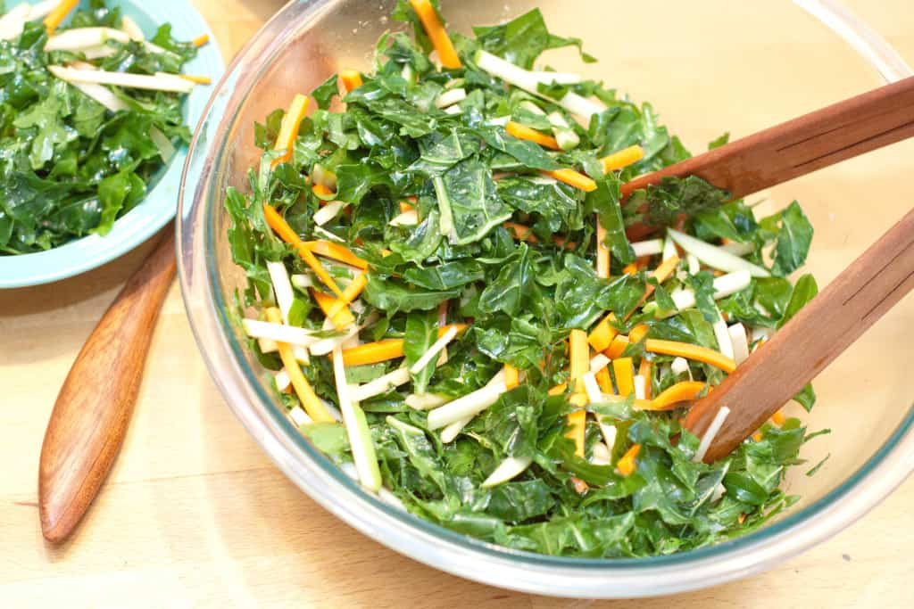 a large bowl of salad with tongs mixed.