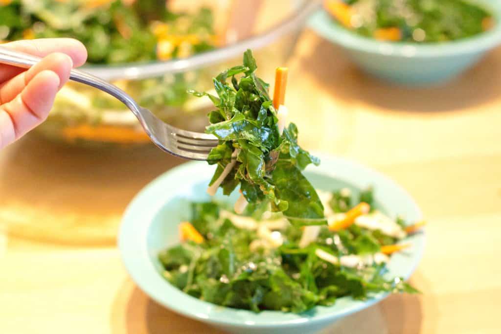 a fork holding up a bite of kale salad.