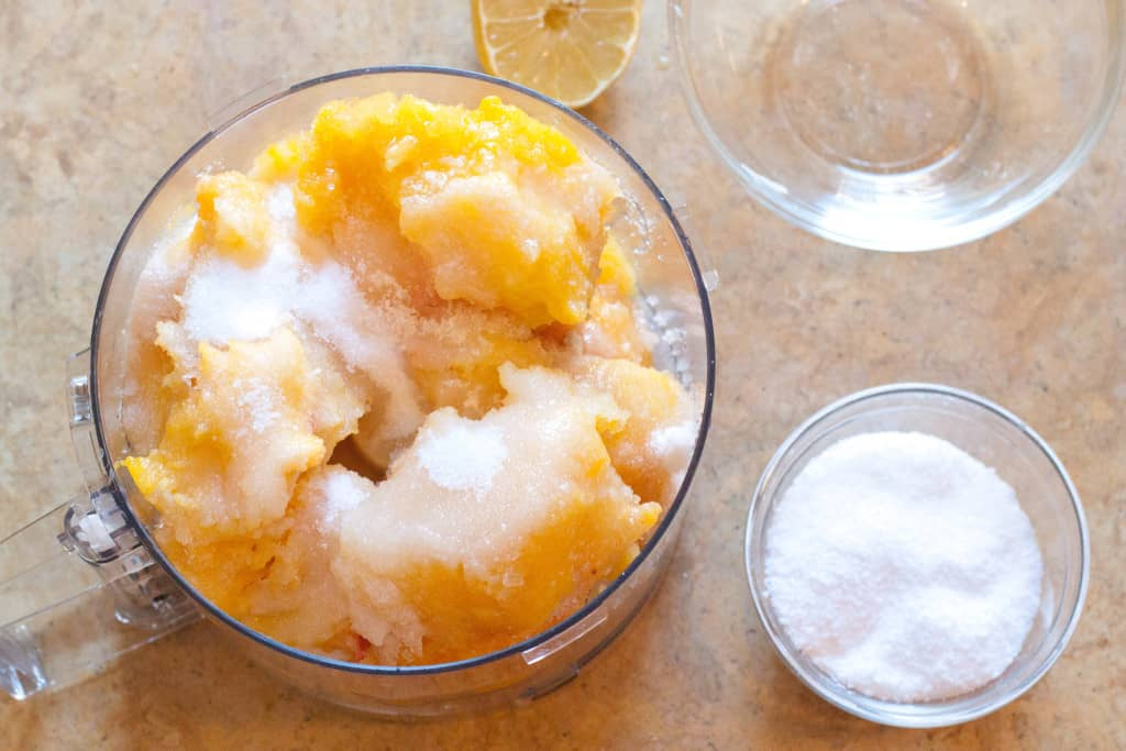 food processor with frozen peaches and sugar