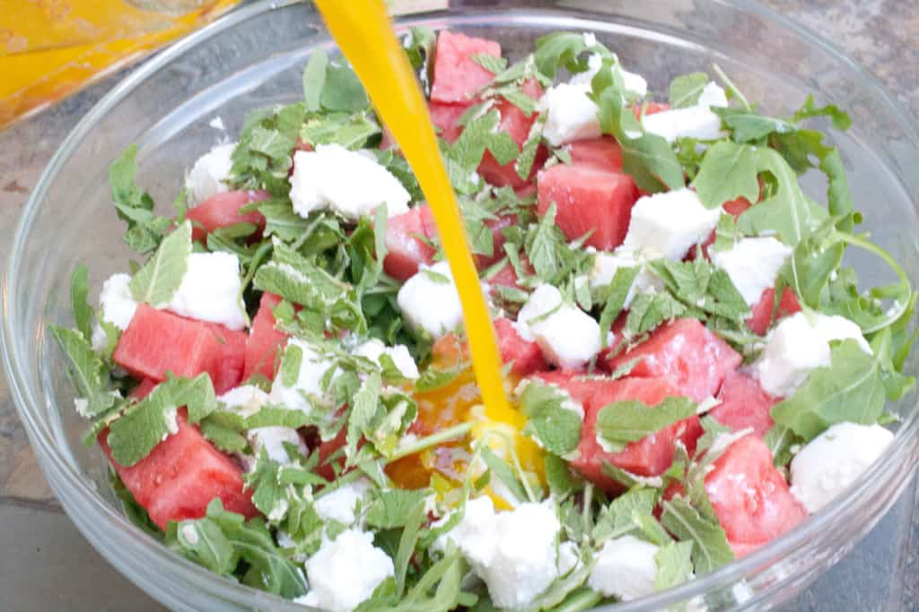 Arugula Watermelon Feta Salad in a large bowl with dressing being poured in