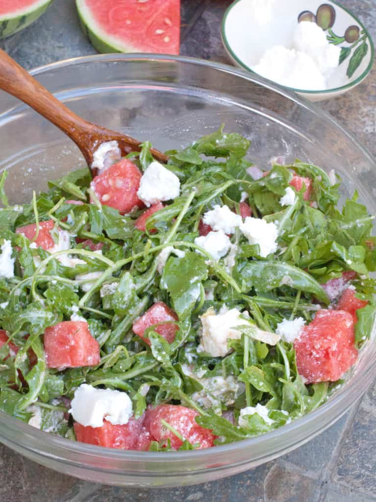 Arugula, Watermelon, and Homemade Feta Cheese n a large bowl with a wooden spoon.