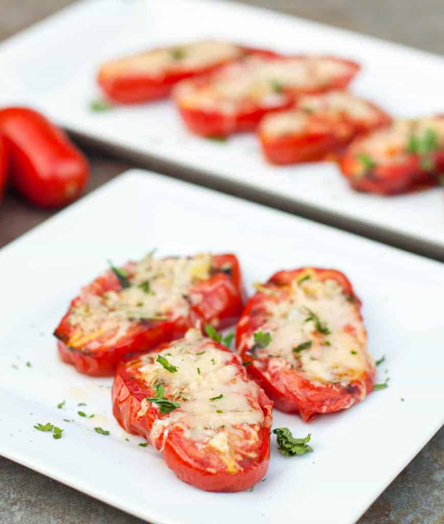 a plate of halved tomatoes with melted cheese on a plate.