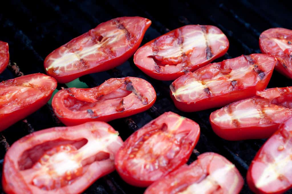 halved tomatoes with grill marks on a grill.