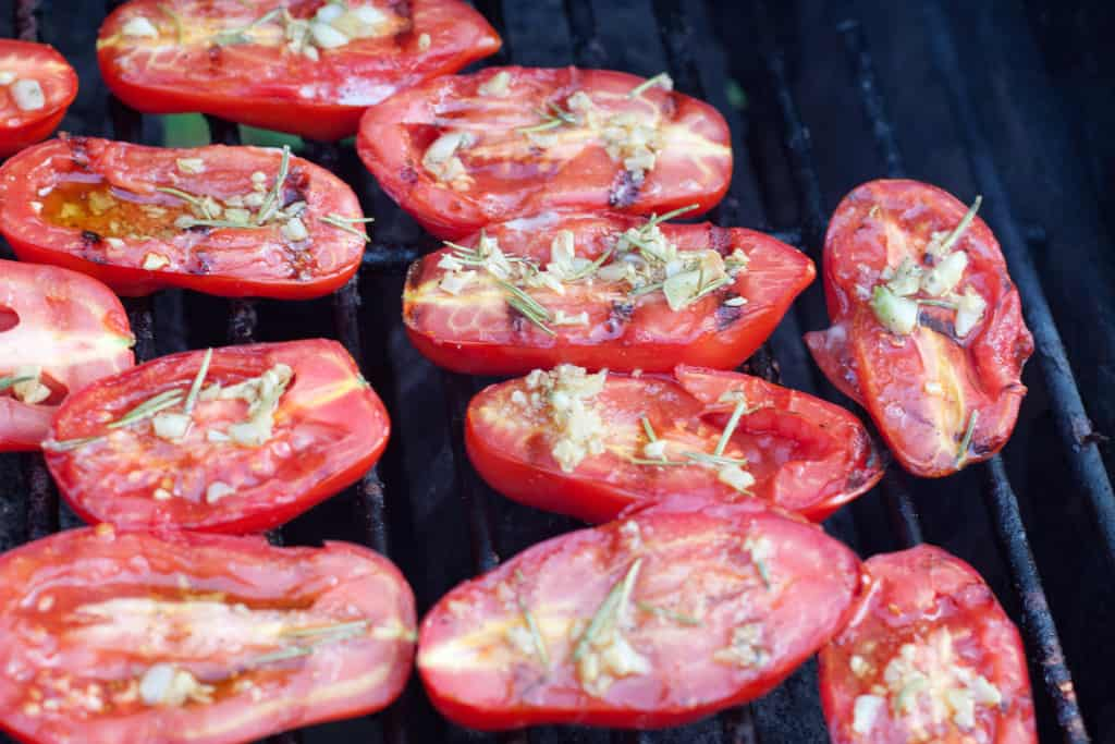 halved tomatoes grilled topped with oil and herbs.