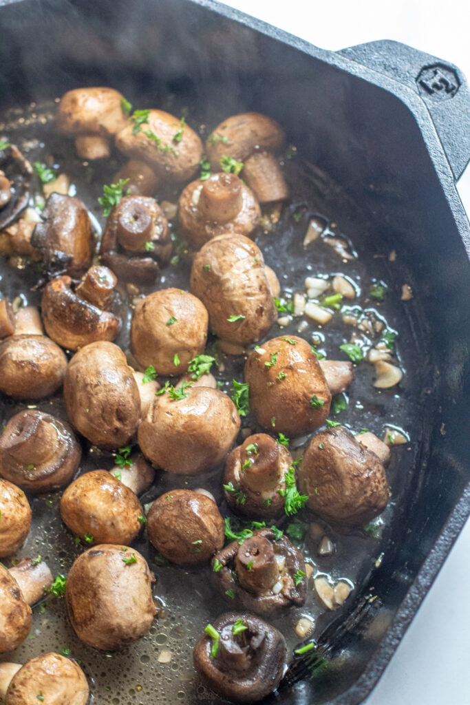 a cast iron with cooked mushrooms in butter and garlc.