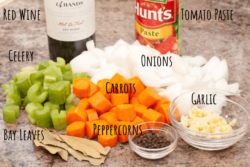 diced carrot, celery, onion on counter with bay leaves, peppercorns, tomato paste, garlic, and bottle of red wine