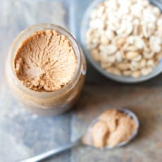open jar peanut butter with spoon and peanuts