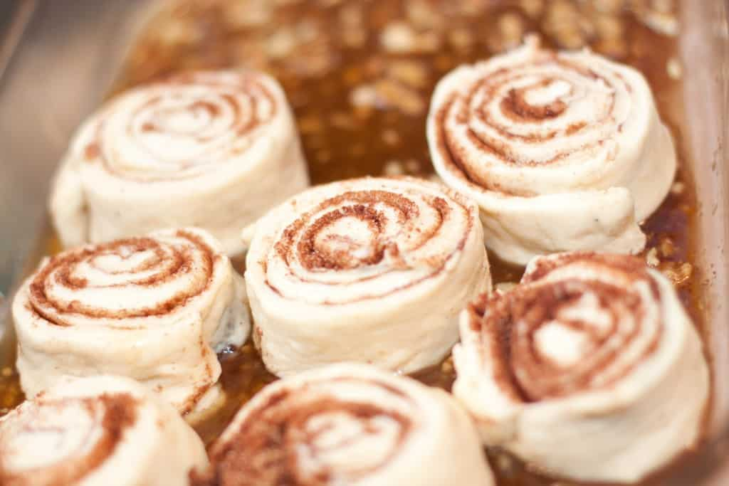 uncooked cinnamon rolls in a glass dish.