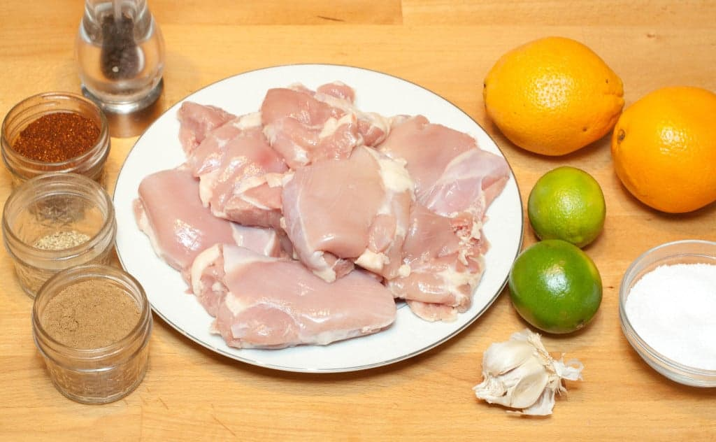 a plate of raw chicken thighs, spices, oranges, limes, garlic, and salt.