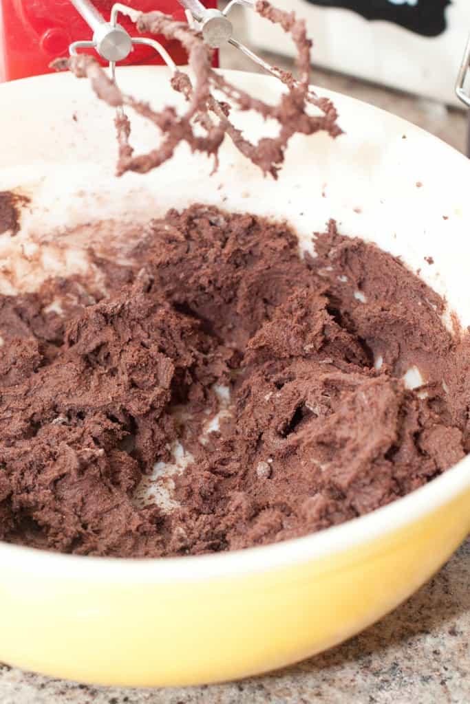 a hand mixer over a bowl of mixed chocolate dough