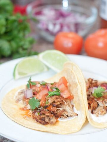 open chicken tacos on plate with tomatoes, onion, and cilantro in background