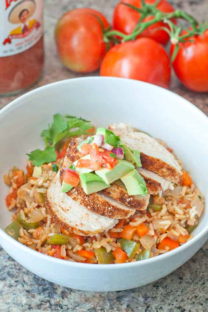 a bowl of rice with peppers and chicken topped with pico and avocado.