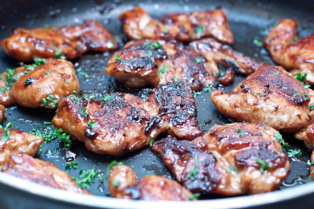 cooked boneless chicken thighs in a pan glazed in soy and maple