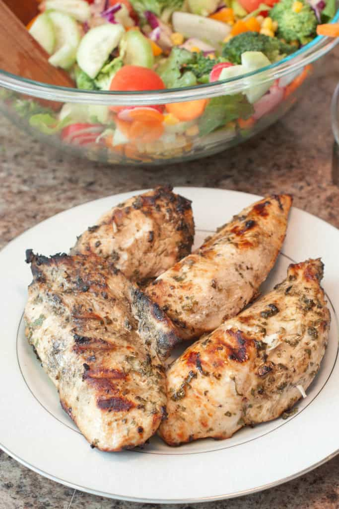 grilled chicken on a plate in front of a salad