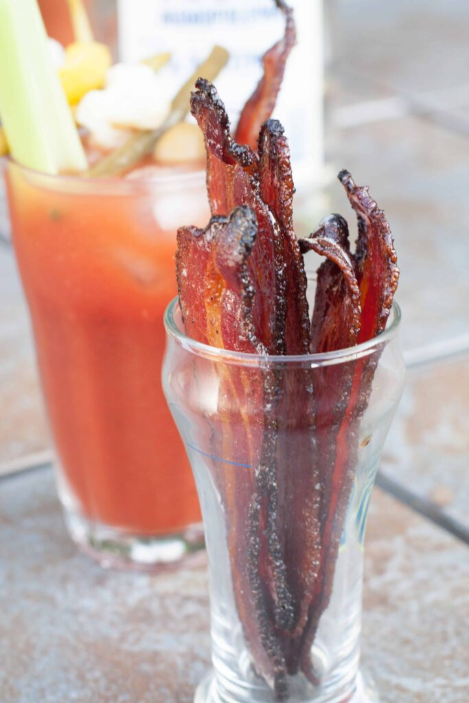 a jar of candied bacon in front of a bloody mary.