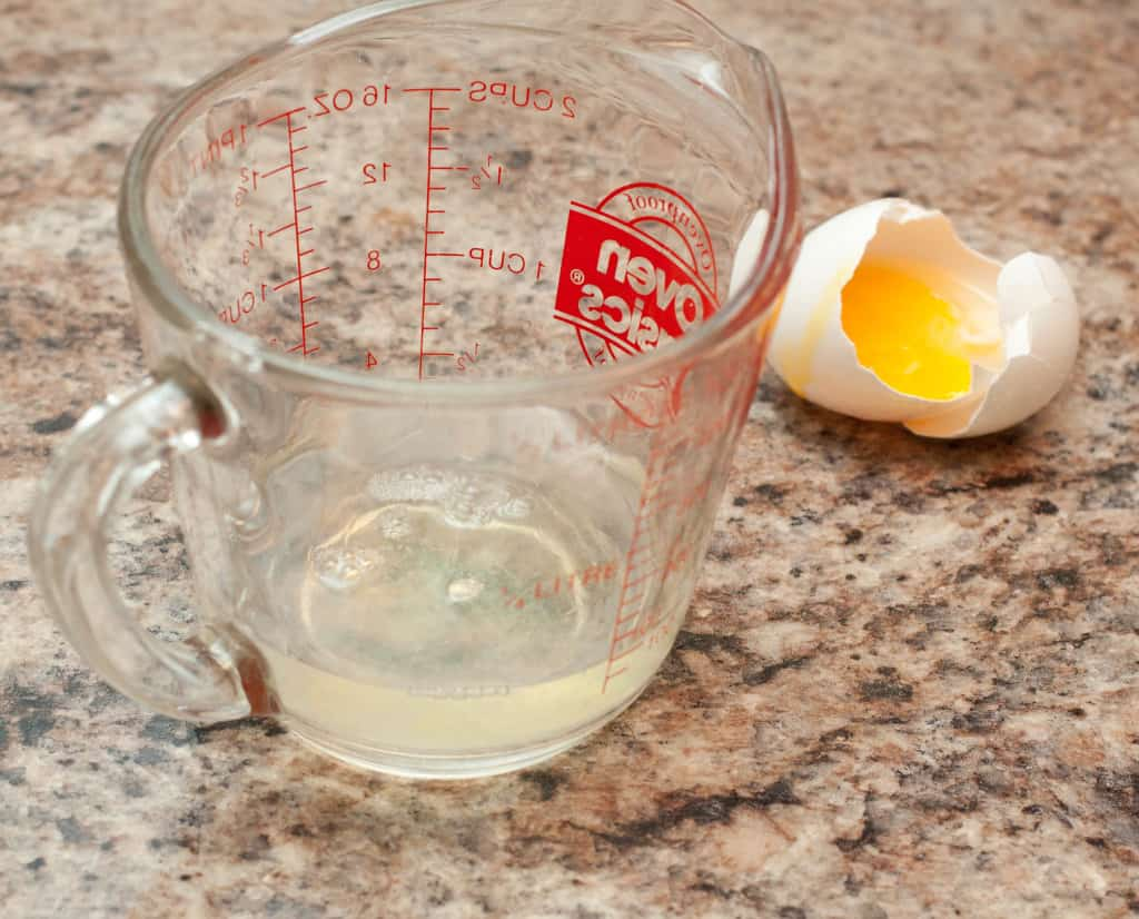 a measuring cup with egg white and a cracked egg and yolk on counter.