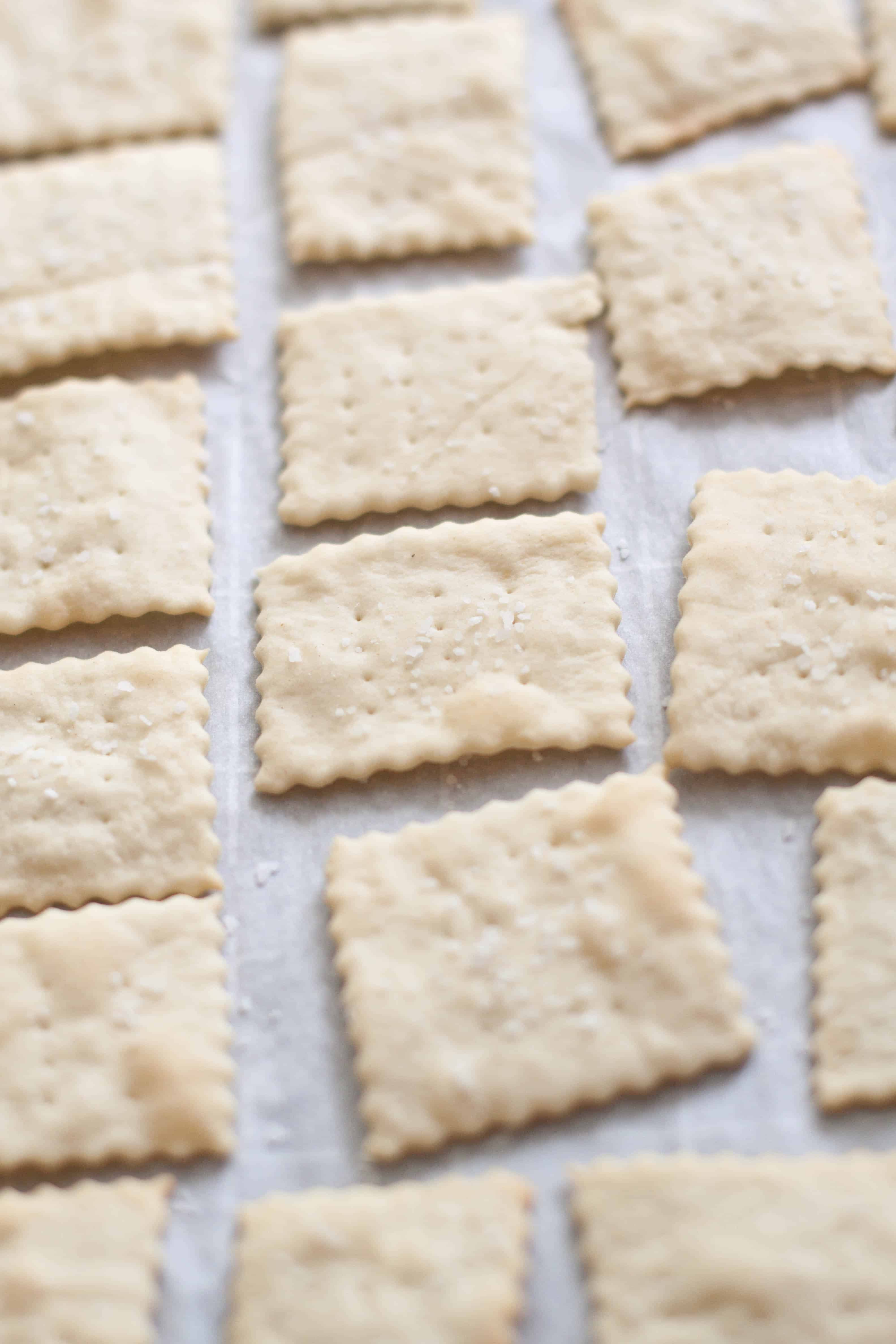 baked saltine crackers lined up on parchment paper
