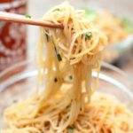 garlic fried noodles held up with chopsticks over a bowl