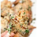 parmesan garlic baked chicken wing held in the air