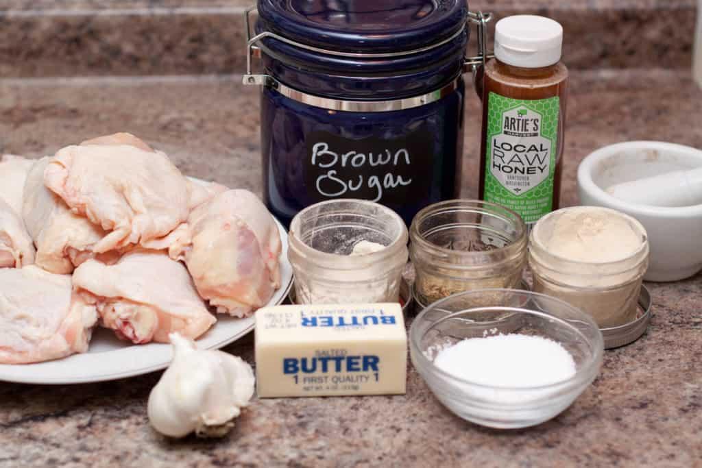raw chicken thighs, butter, garlic, salt, spices, sugar, and honey on counter.