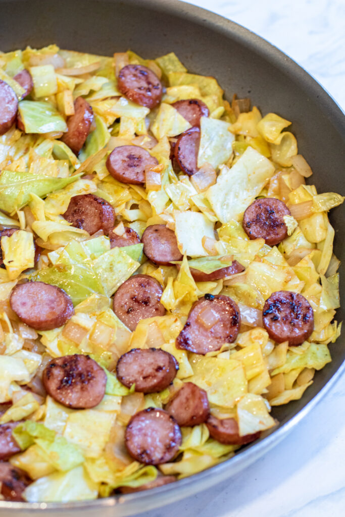 overhead of large pan with cooked kielbasa and cabbage