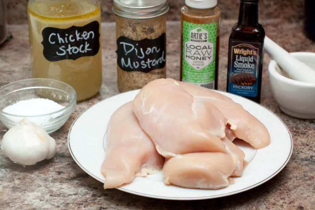 chicken stock, raw chicken, mustard, honey, liquid smoke, salt, and garlic on a counter