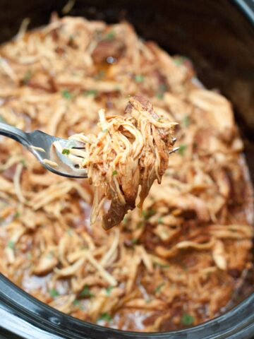 a fork holding up cooked shredded chicken