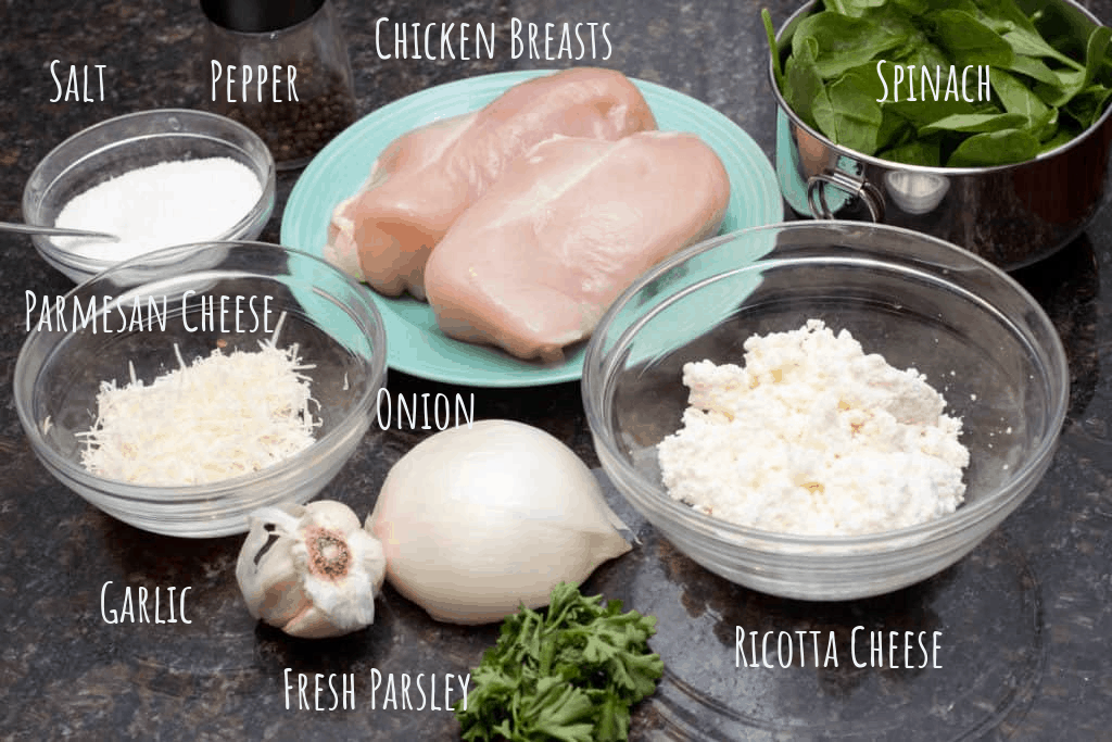 chicken breasts, spinach, ricotta cheese, parm cheese, garlic, onion, salt, pepper, and parsley on a counter