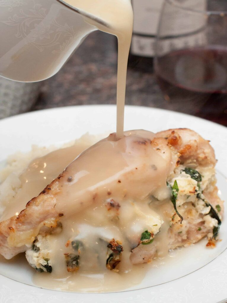 a plate with stuffed chicken with gravy being poured on it