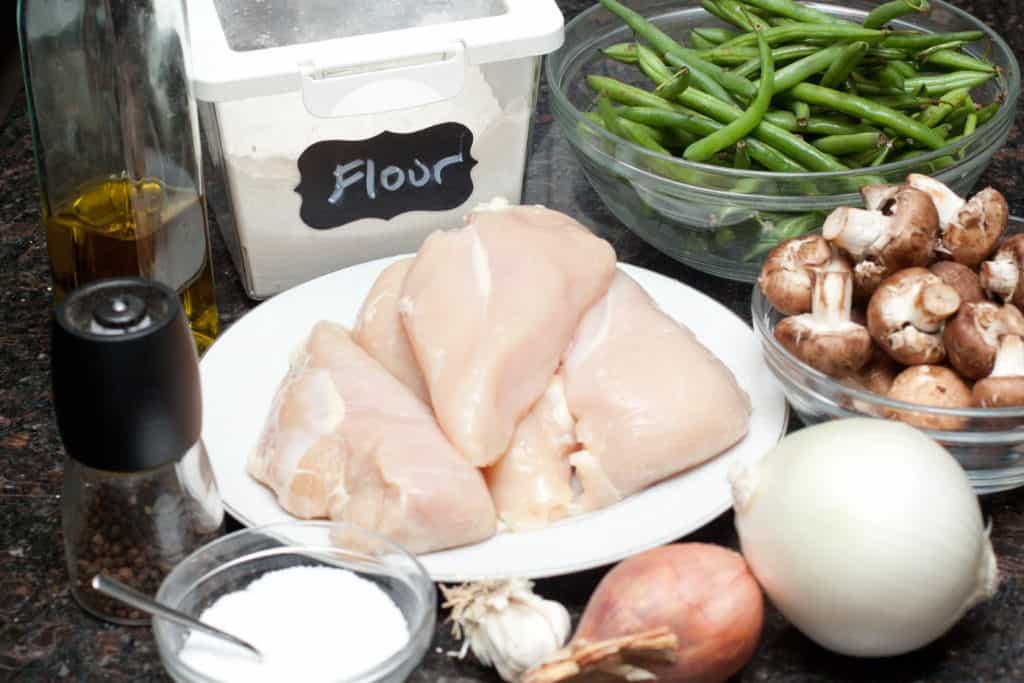 raw chicken, flour, green beans, mushrooms, onions, garlic shallots on counter.
