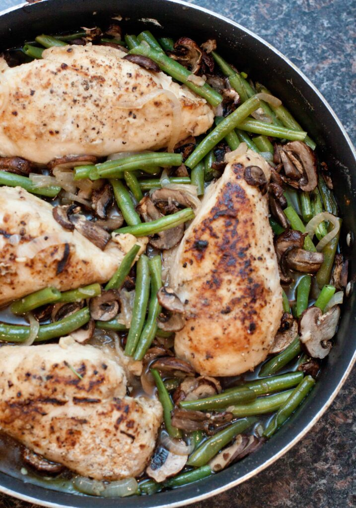 overhead of cooked chicken breasts with green beans and mushrooms in a skillet.