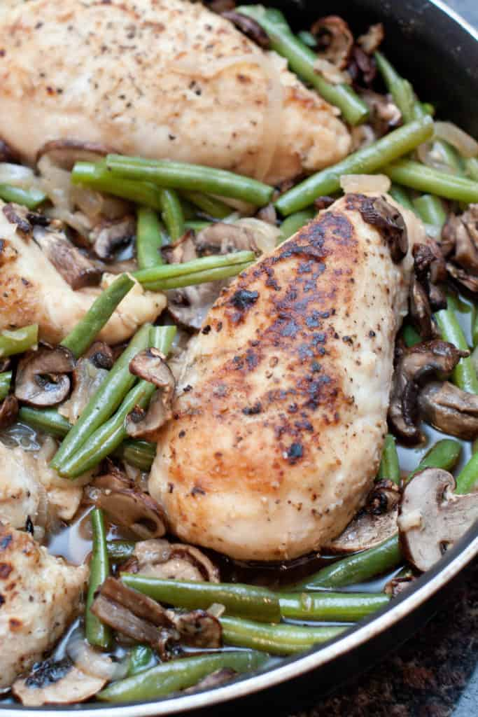 cooked chicken breasts with green beans and mushrooms in a skillet.