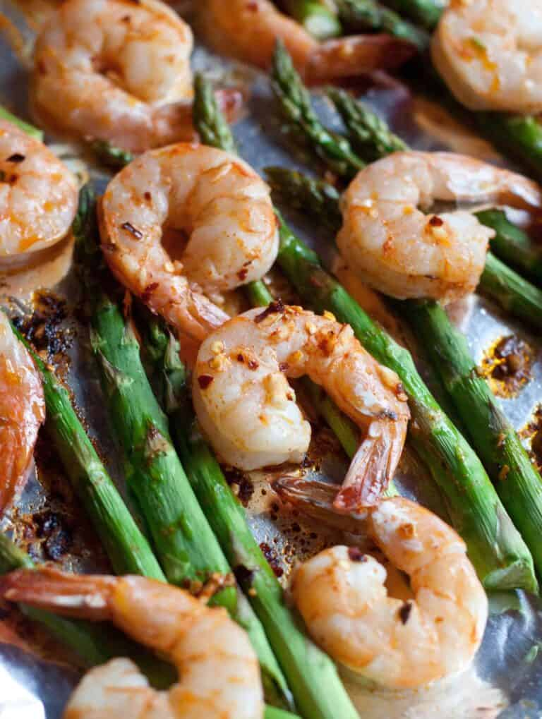 a close up of cooked shrimp and asparagus on a baking sheet.