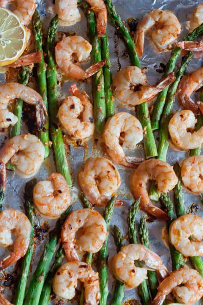 an overhead of cooked shrimp and asparagus.