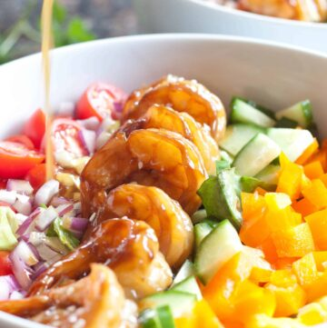 teriyaki shrimp salad in a bowl with dressing poured on top