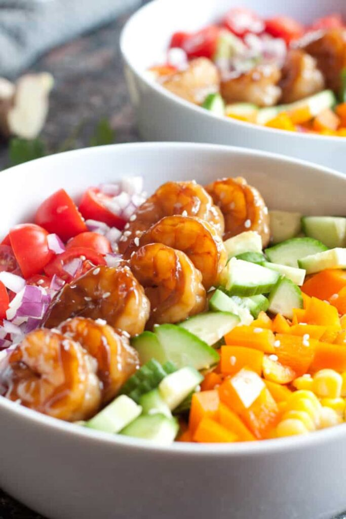 bowl with shrimp and colorful chopped vegetables.
