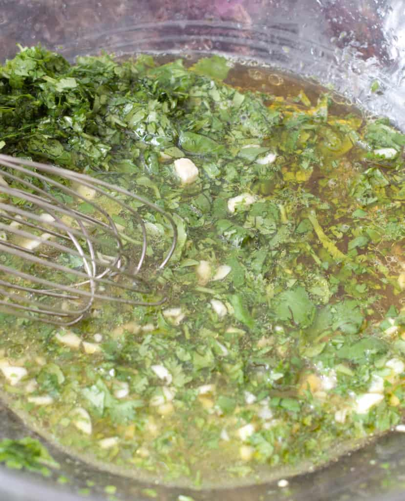a bowl of cilantro, garlic, olive oil, honey, salt, lime juice all mixed together