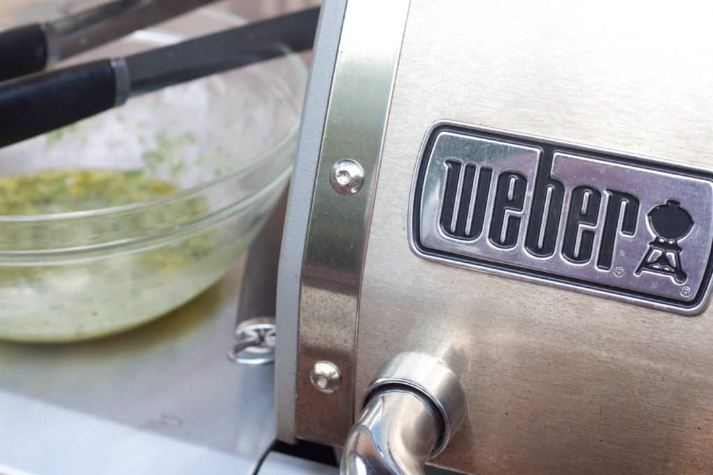 a bowl of marinade and a close up of a weber grill