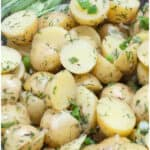 cooked potatoes topped with onions, dill, and scallions in a bowl
