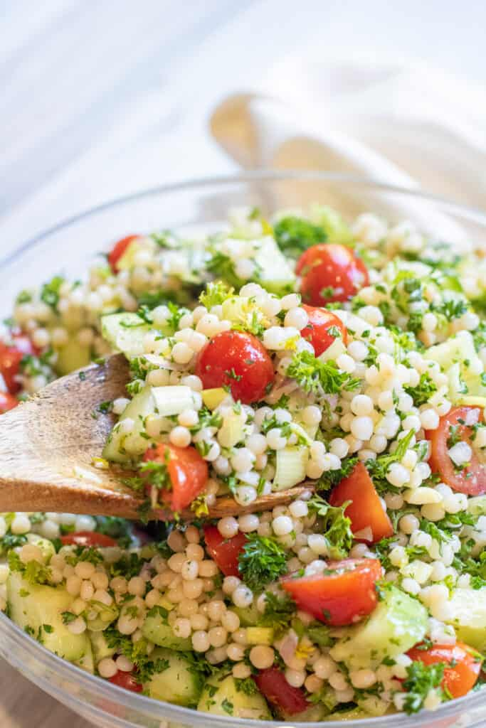 a wooden spoon holding some couscous with tomatoes and cucumbers.